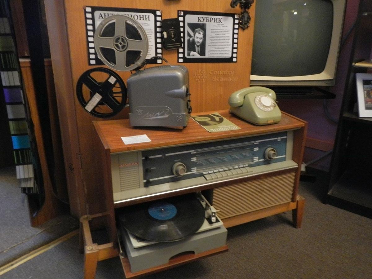 музей 60 годов. Радиола с встроенным проигрывателем, грампластинка. Кинопроектор, телефон и телевизор сбоку.