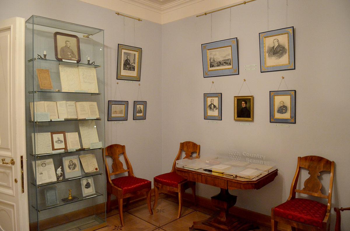 Квартира Пушкина на Арбате – столик и стулья, портреты и пейзажи на стенах, стеллаж с публикациями.