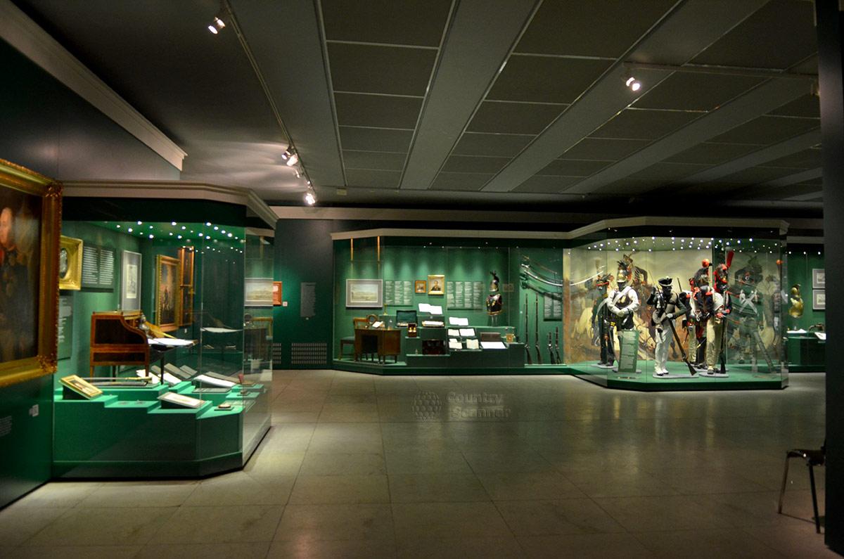 Экспозиционный зал музея бородинской панорамы. Несколько витрин с экспонатами, справа – группа манекенов в военной форме и с оружием – солдаты обеих армий.