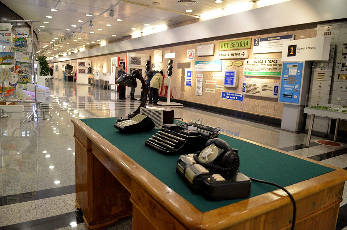 Экспозиционный зал музея метро. На первом плане старинный стол диспетчера и оргтехника давних времен.