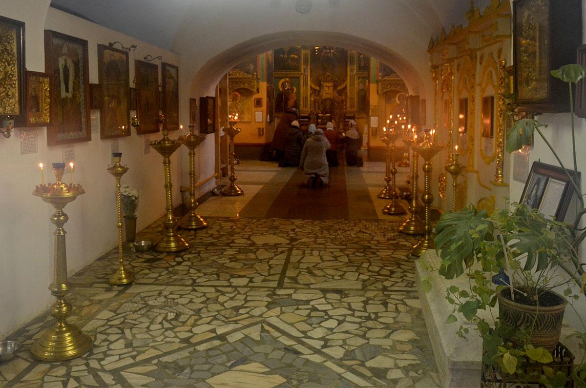 Иконостас алтаря церкви Иоанна Богослова в Костроме, коленопреклоненные молящиеся прихожане. На переднем плане подсвечники перед образами православных святых.