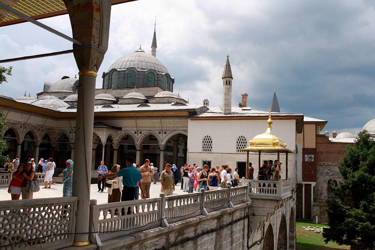 Туристы, любующиеся морскими видами с террасы во дворце Топкапы. Под позолоченной крышей – Беседка султанов.