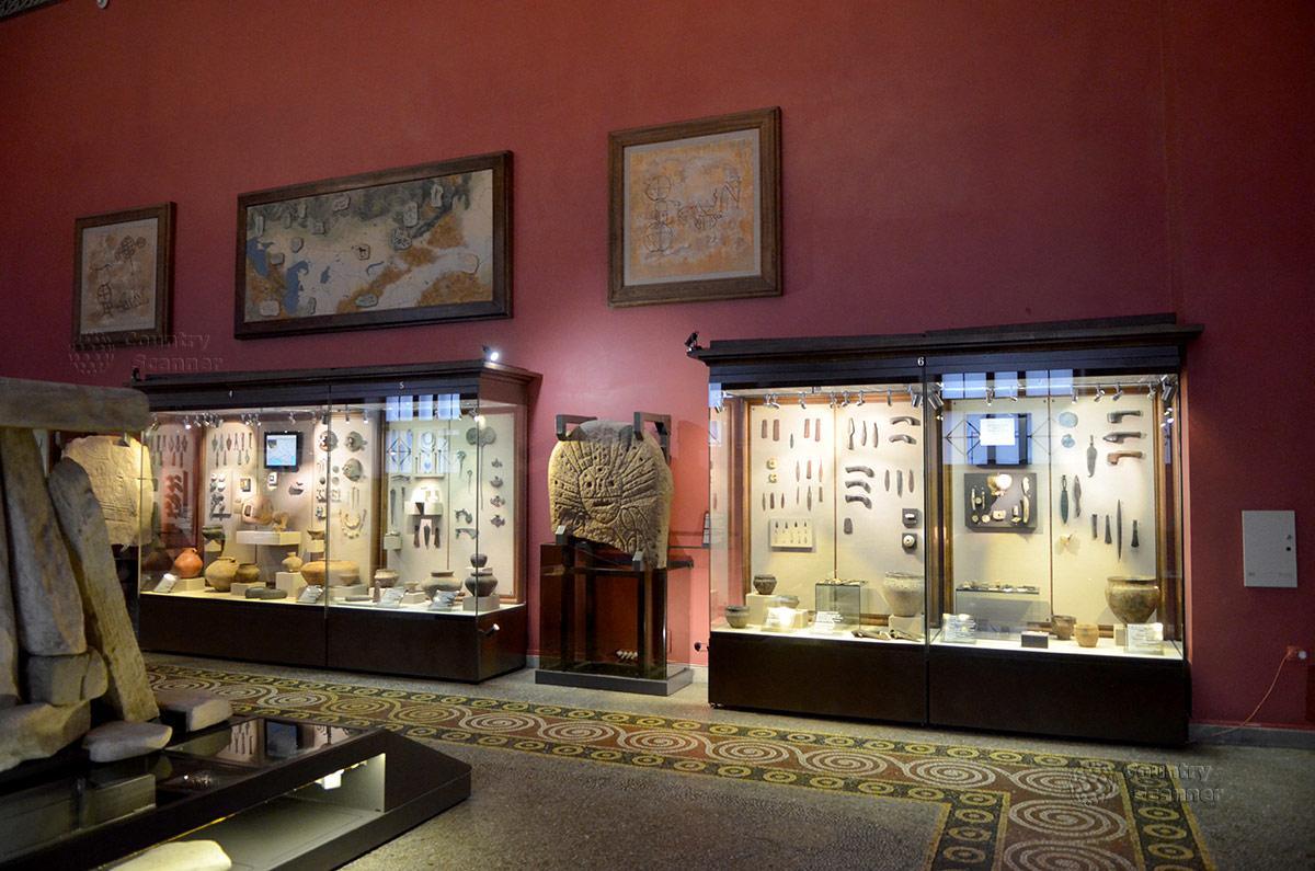 Витрины экспозиции истории древнего мира в государственном историческом музее. В середине – каменная глыба с изображением языческого Бога Солнца.
