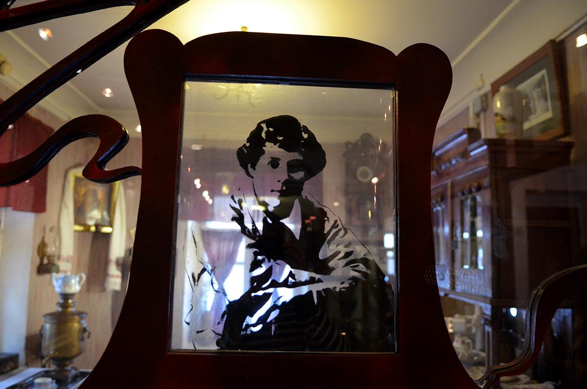 Музей Есенина. Нанесенная на стеклянную перегородку фотография поэта в массивной рамке. Мемориальную комнату можно только осматривать через стекло, как объемную витрину.