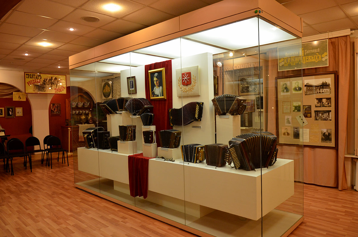 Общий вид экспозиционного зала в музее гармоники. Исторические экспонаты в витринах и на стендах.