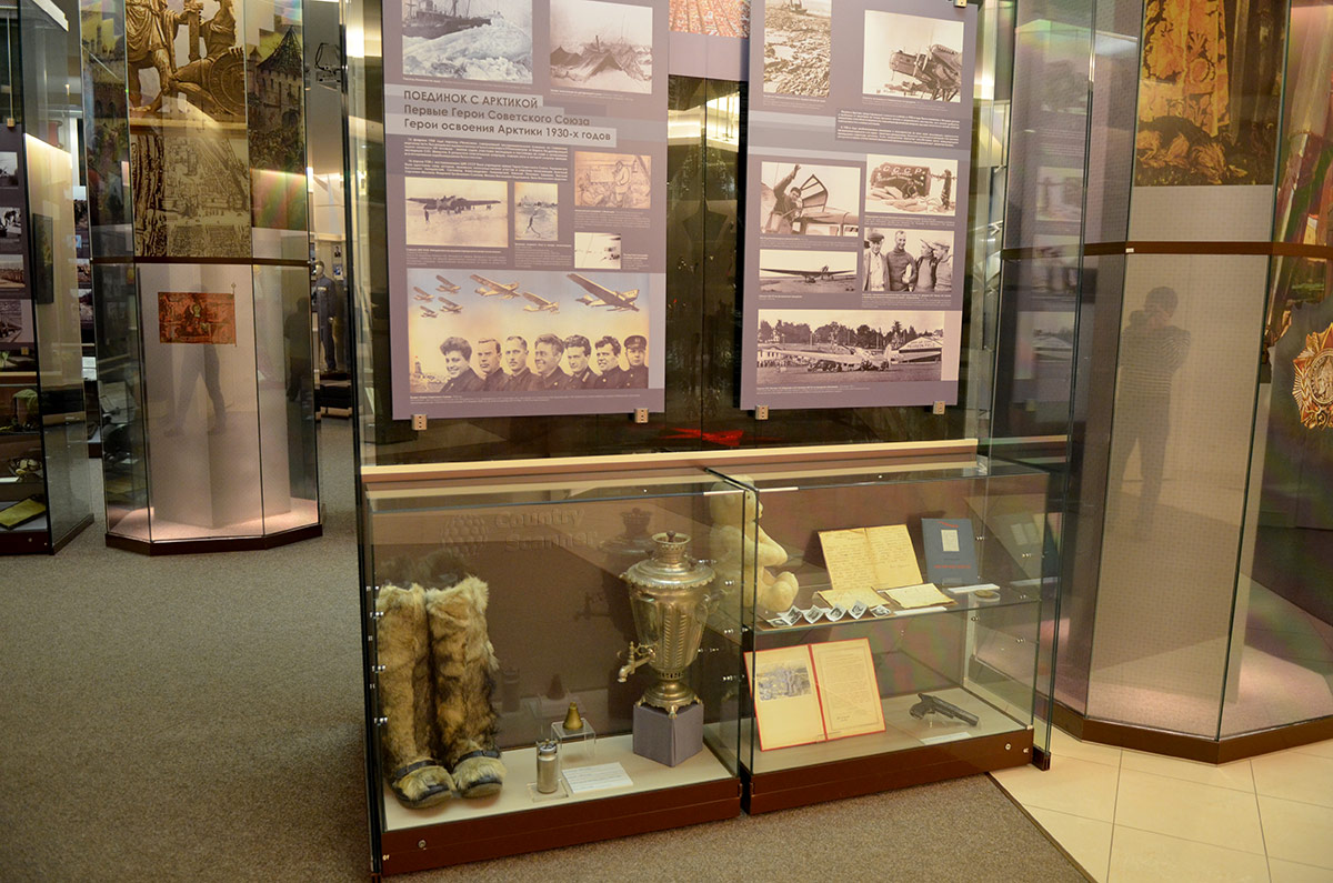 Информация о первых обладателях высокого звания – полярных летчиках на стенде музея Героев. Нижняя витрина содержит необходимые в арктических условиях предметы одежды и обихода.