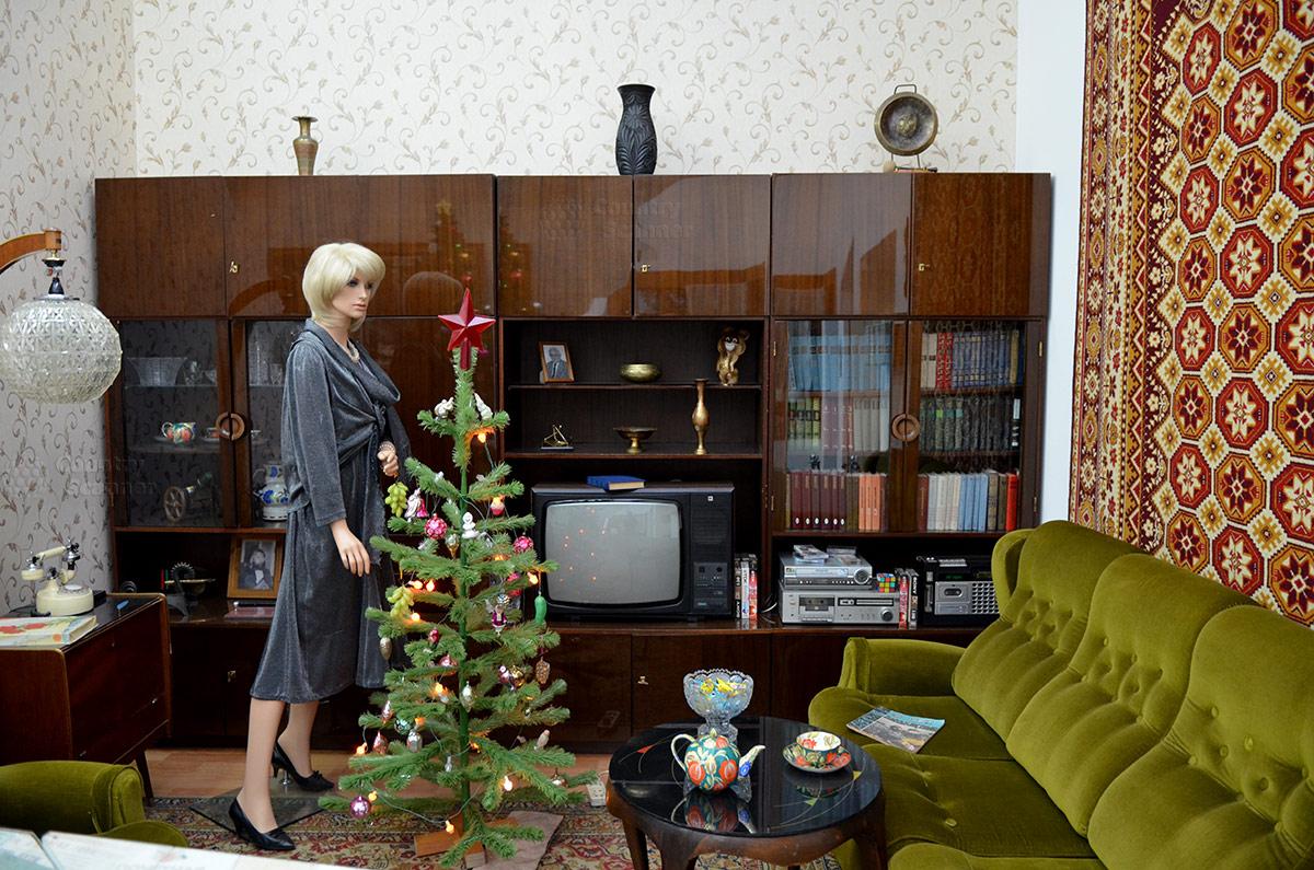 Музей Пресня, гостиная в квартире 80-х годов. Более современная бытовая техника и предметы обстановки, одежда и прическа хозяйки помещения.