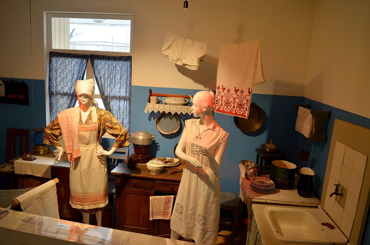 Музей Пресня. Беседующие соседки на кухне коммунальной квартиры, скудная обстановка помещения общего пользования для нескольких семейств.