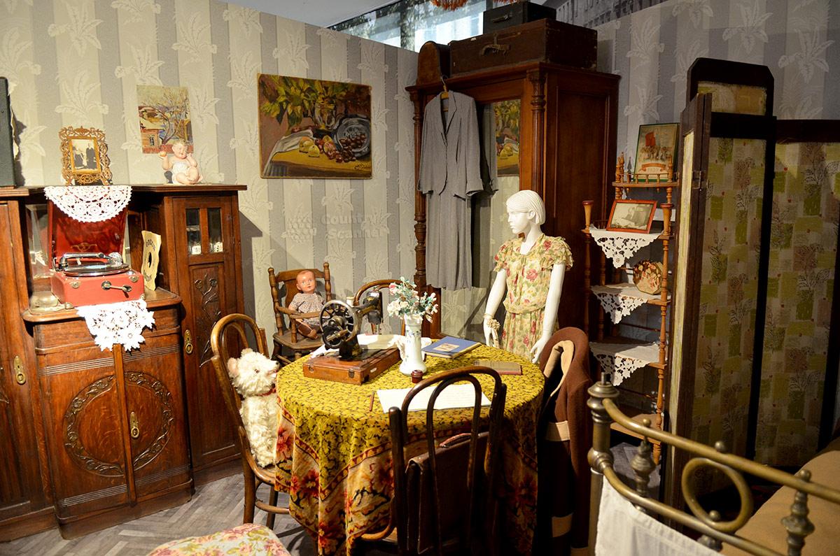 Хозяйка одной из комнат коммунального жилища в своем помещении, одновременно гостиной и спальне, в музее Пресня в Москве.