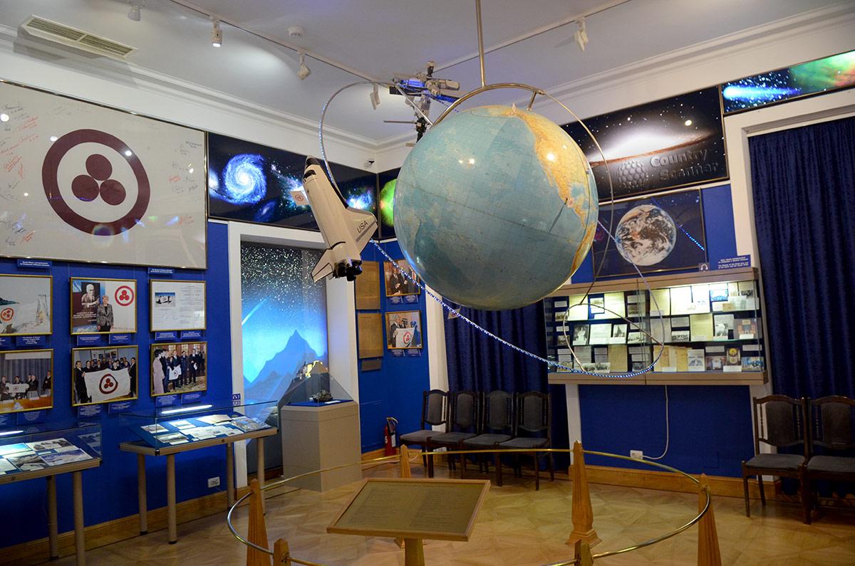 Зал Знамени Мира в музее Рериха. Облик вселенной на настенных планшетах и наша планета в виде модели земного шара, вращающегося на своей орбите. Эмблема на знамени – триединство, имеющее несколько толкований.