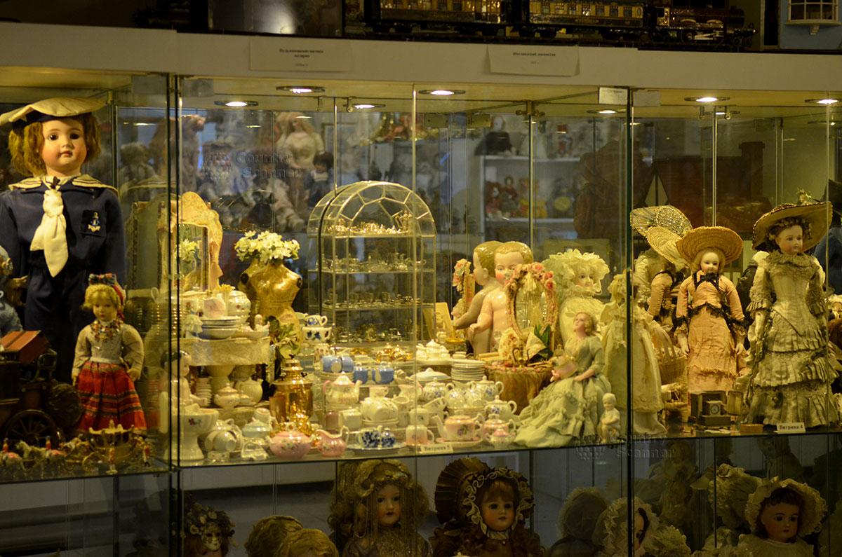 """Музей уникальных кукол. Витрина со старинными сервизами и """"живыми"""" куклами."""