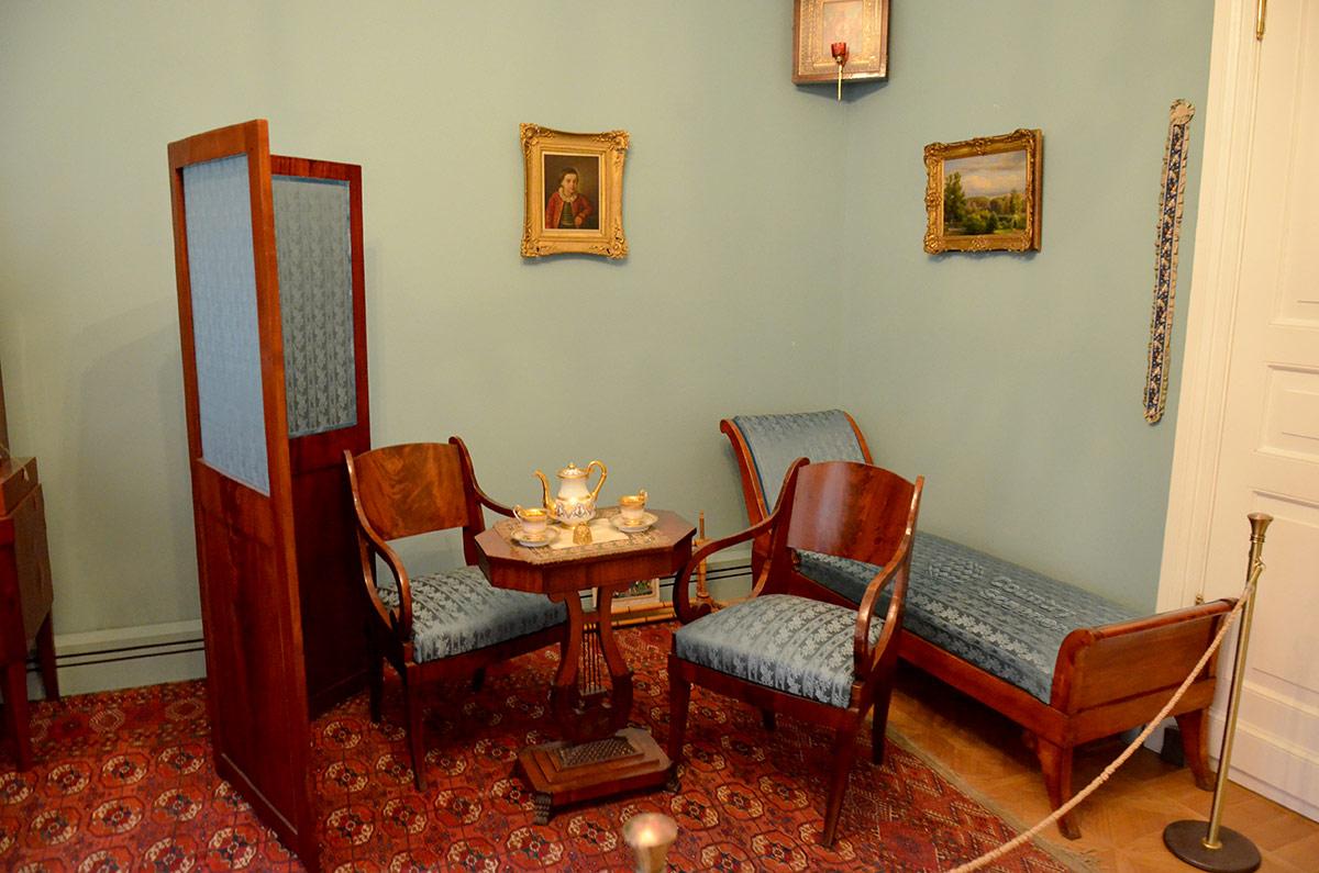 Уголок отдыха в комнате бабушки поэта. Мебельдля отдыха добротна, особенно интересна подставка чайного столика. На стене один из портретов музея Лермонтова, изображающий его в детском возрасте.