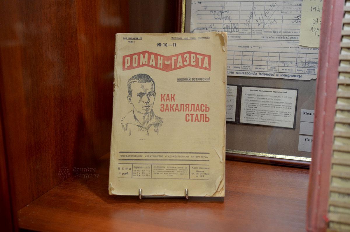 В витрине шкафа можно увидеть первую публикацию знаменитого романа, осуществленную Роман-газетой. Рядом трафарет, придуманный Островским для предотвращения сползания рукописных строк.