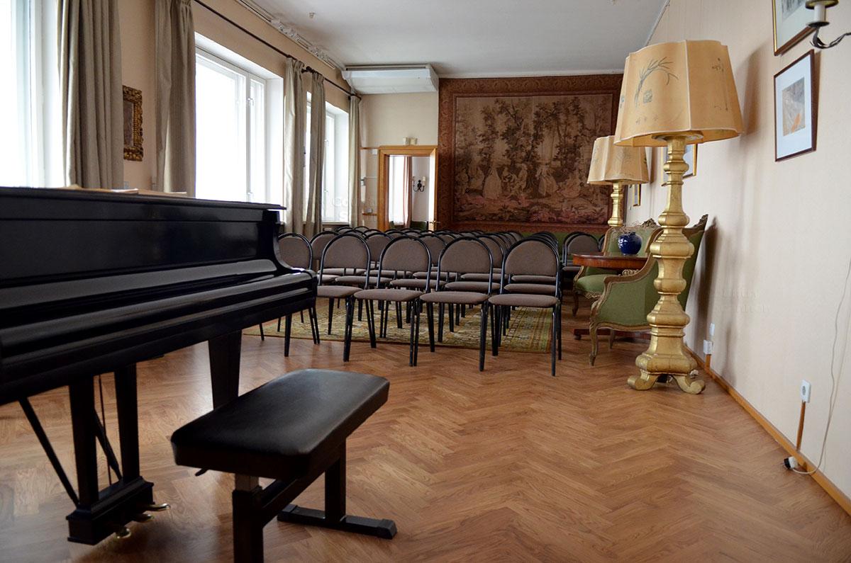 Концертный рояль, ряды зрительских стульев для гостей и участников музыкальных мероприятий в мемориальной квартире Святослава Рихтера. Мебель, гобелен на стене и торшеры, подаренные мэром Флоренции.