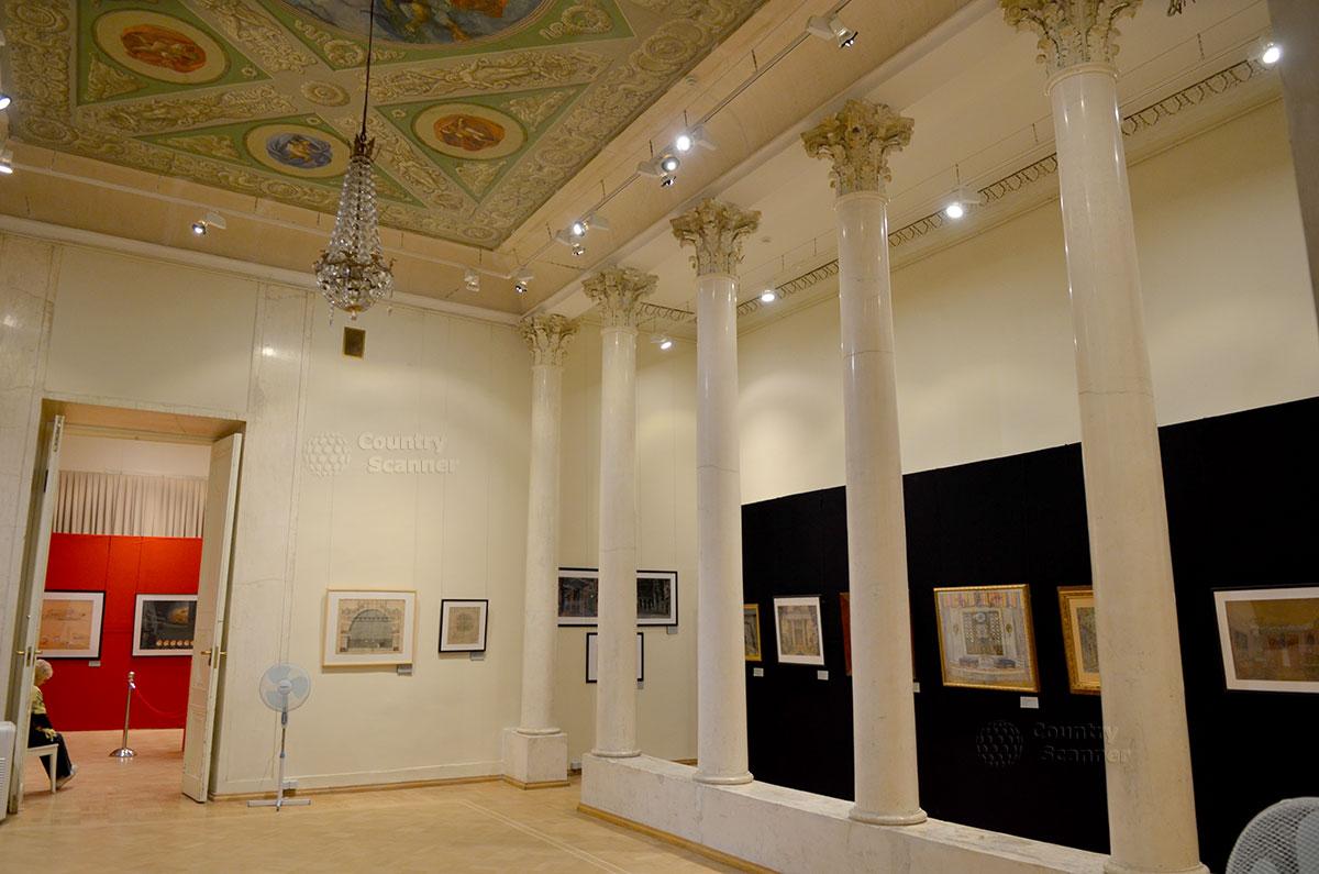 Один из залов архитектурного музея с самым замечательным интерьером. Череда мраморных колонн с красочными капителями сочетается с расписным потолком и хрустальной люстрой.