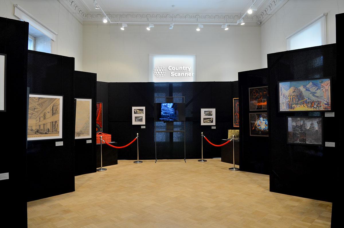 Ряды экспозиционных стендов в архитектурном музее, заполненные выставочными работами. Черный фон прекрасно оттеняет представленные материалы.