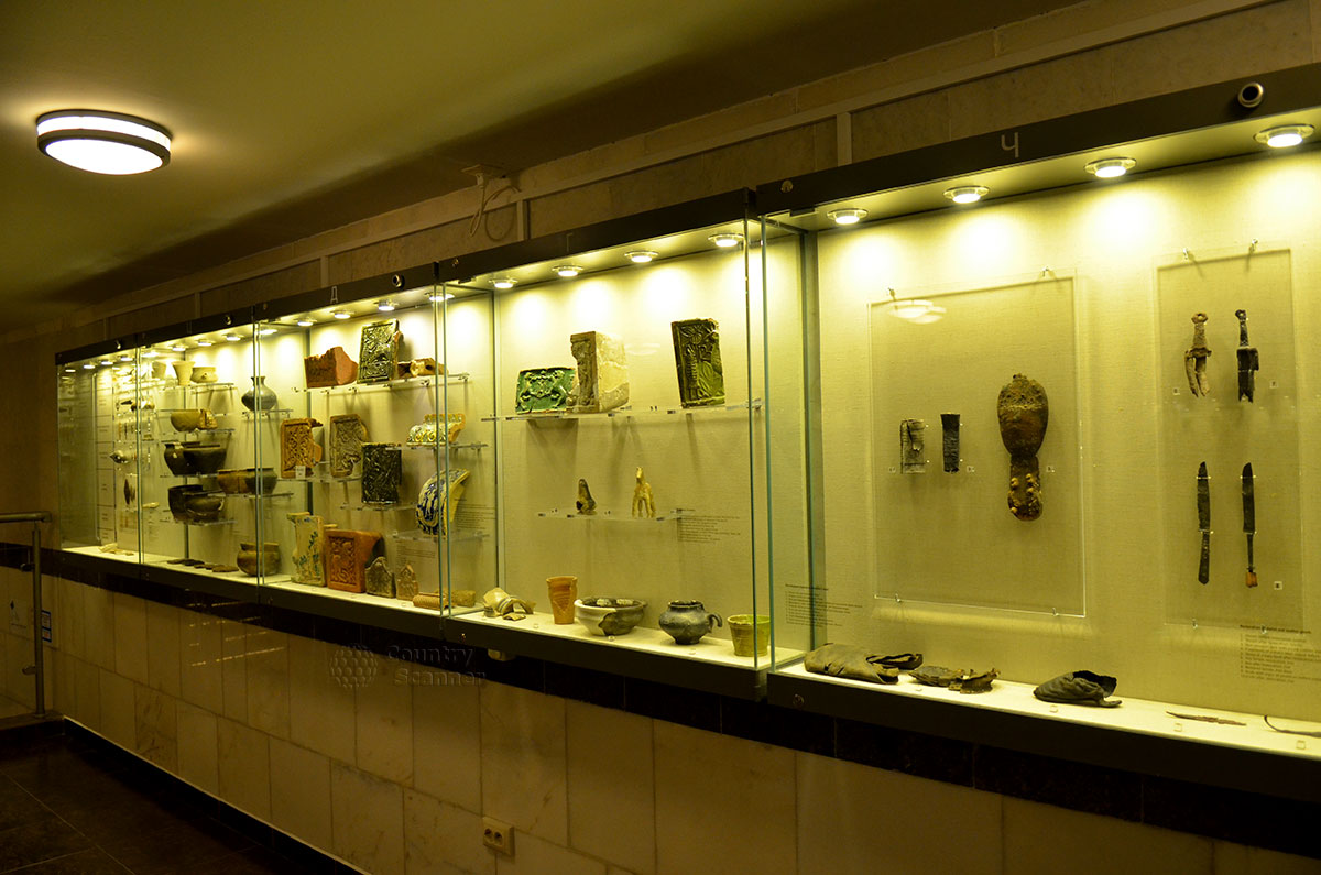 Музей археологии Москвы, витрина с экспонатами, наиболее близкими по происхождению к нашему времени. Керамические изразцы и различные сосуды, обувь из кожи и бытовые предметы.