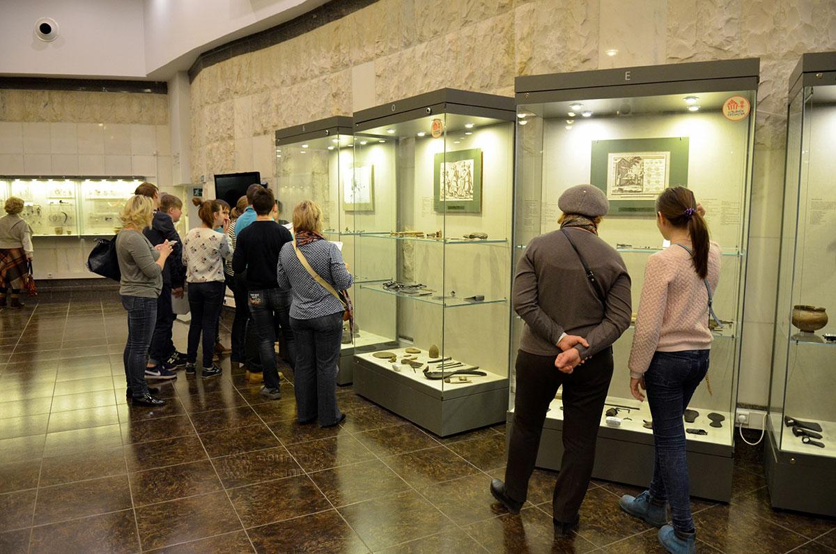 Посетители музея археологии Москвы возле витрины с экспонатами, найденными при исследовании фундамента и некрополя древнего Моисеевского монастыря.