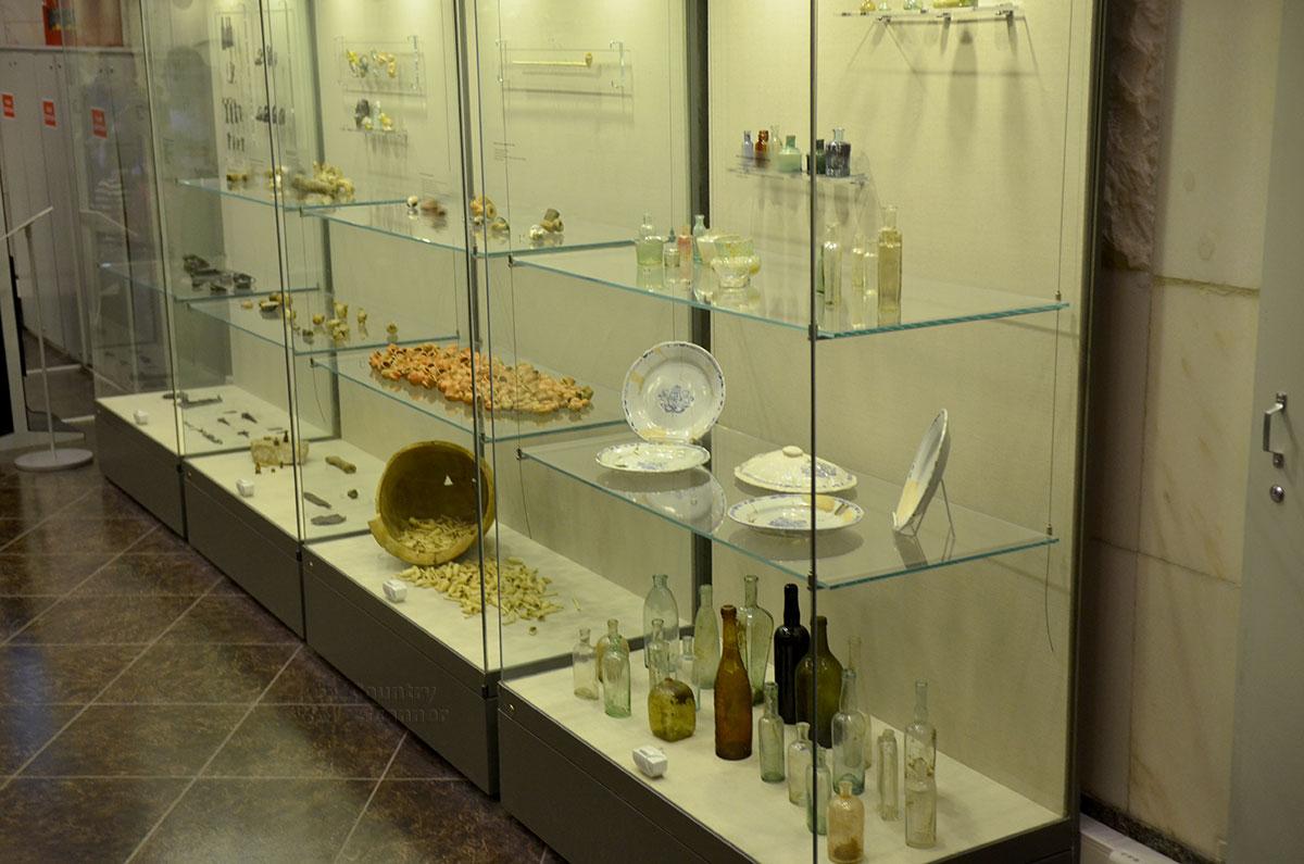 Витрина музея археологии Москвы, в которой найденные предметы сгруппированы по принципу их функционального назначения. Бутыли и пузырьки, курительные трубки соседствуют с настоящим кладом древних монет.