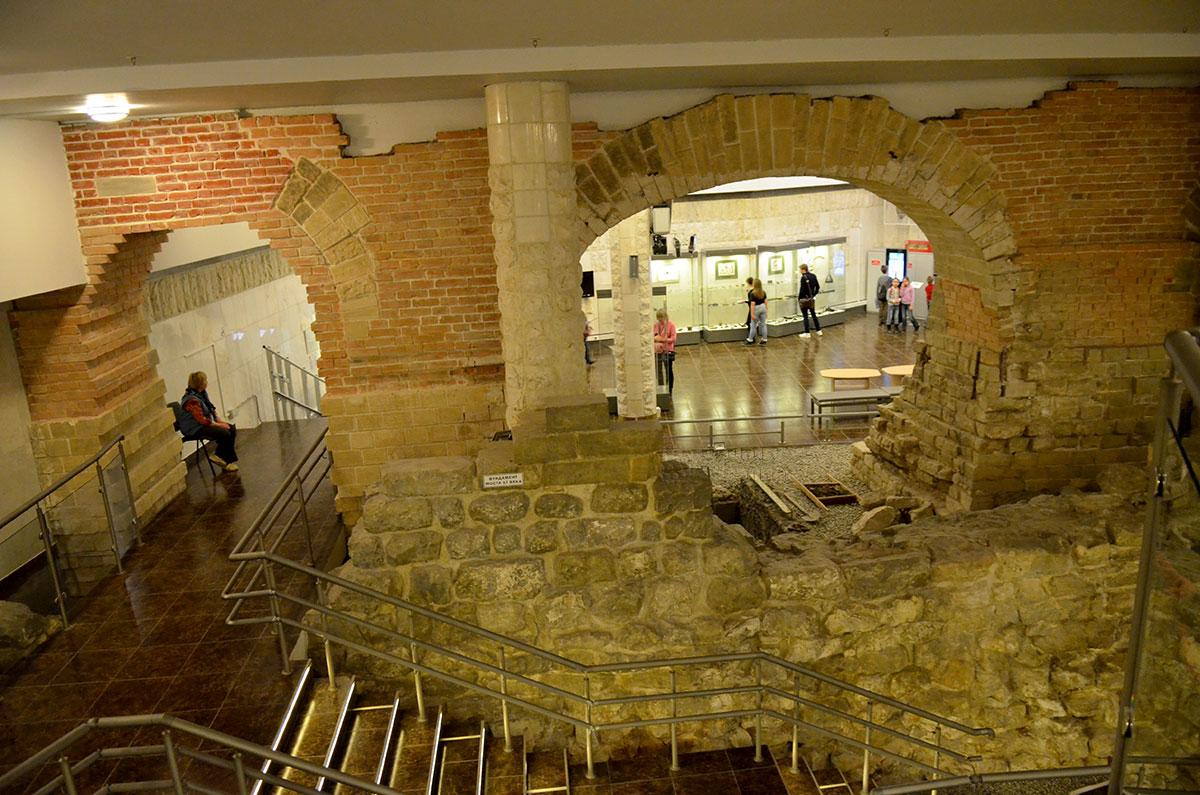 Обзорный вид древних стен, встроенных в помещение музея архитектуры Москвы. В проеме виден соседний зал, лестницы и переходы между различными помещениями.