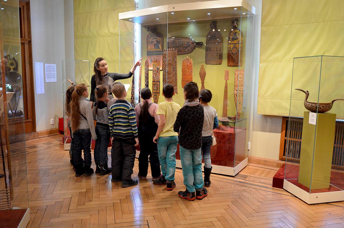 Юные посетители музея декоративно-прикладного и народного искусства внимательно слушают пояснения экскурсовода у стенда образцов ручных прялок.