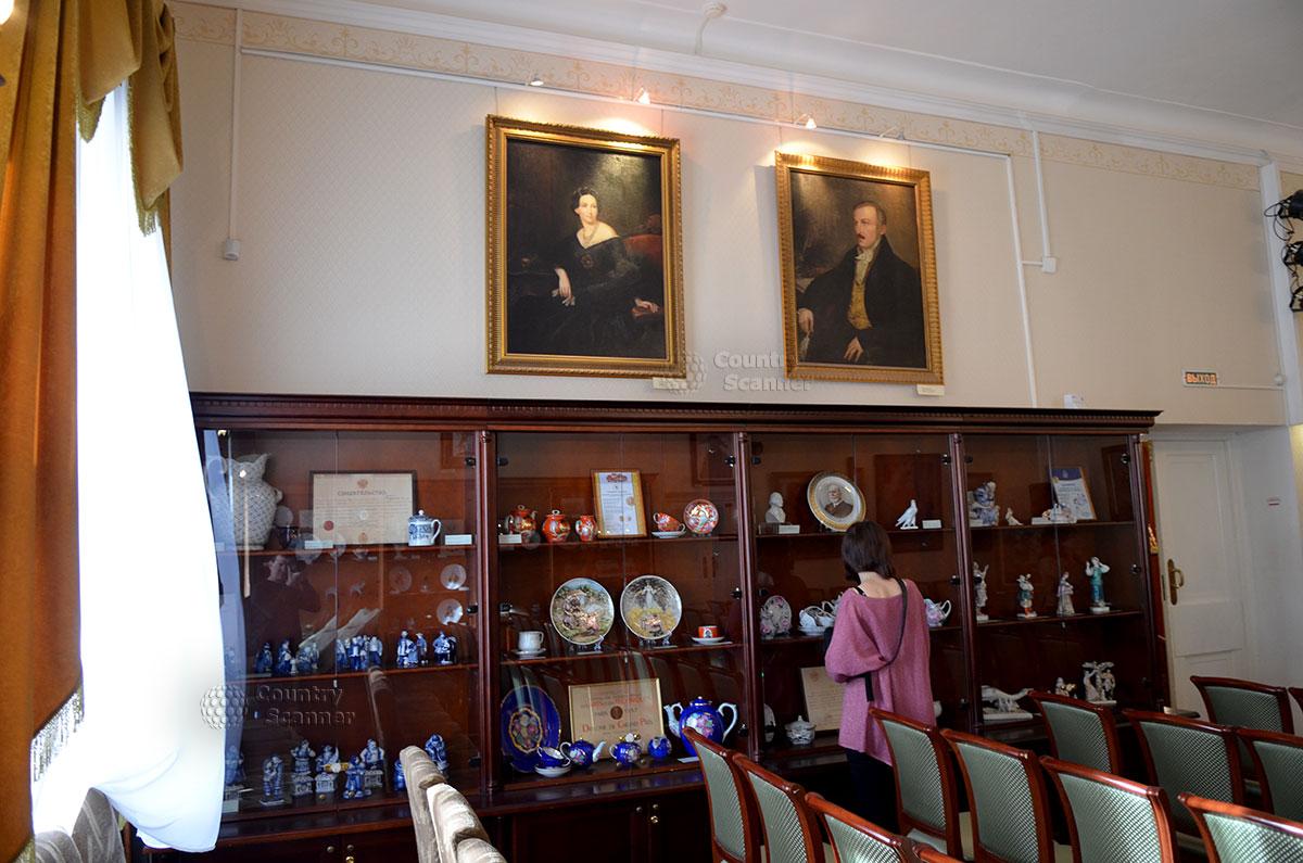 Витрины музея Гоголя, посвященные коллекции фарфоровых изделий семейства хозяев особняка. На стене портреты сенатора, графа Алексея Петровича Толстого и его супруги.