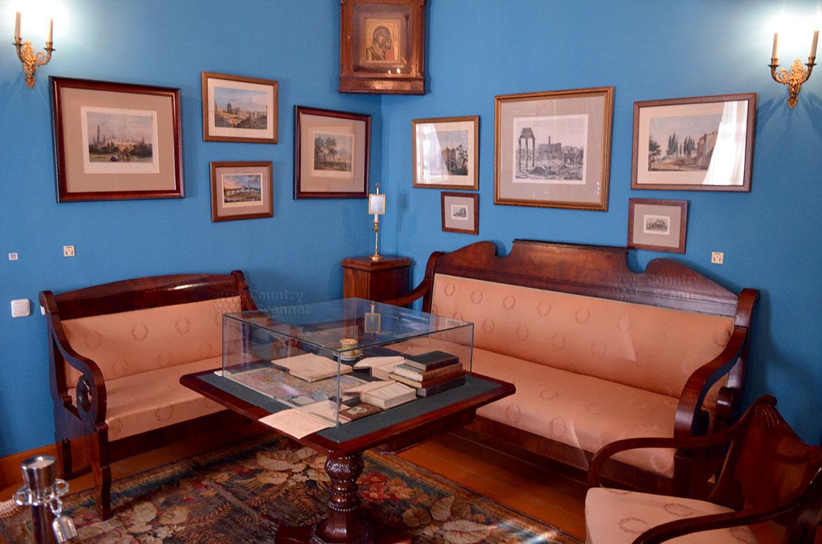 Под иконой вывешены изображения тех мест, где побывал писатель во время своих путешествий. Помещение гостиной в музее Гоголя в Москве.