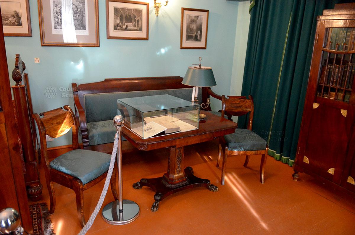 Московский музей Гоголя. Письменный стол и мягкая мебель в кабинете писателя, где он работал в моменты утомления от письма стоя. Гармония окраски стен, обивки мебели и даже абажура настольной лампы.