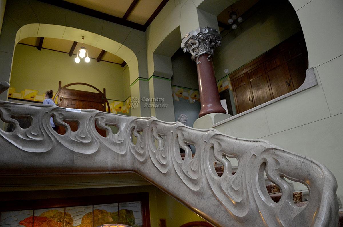 Мраморные перила в форме морских волн на лестнице музея Горького. На фоне зеленоватой, цвета морской воды окраски стен выделяется колонна из темного мрамора и особенно ее красочная капитель.
