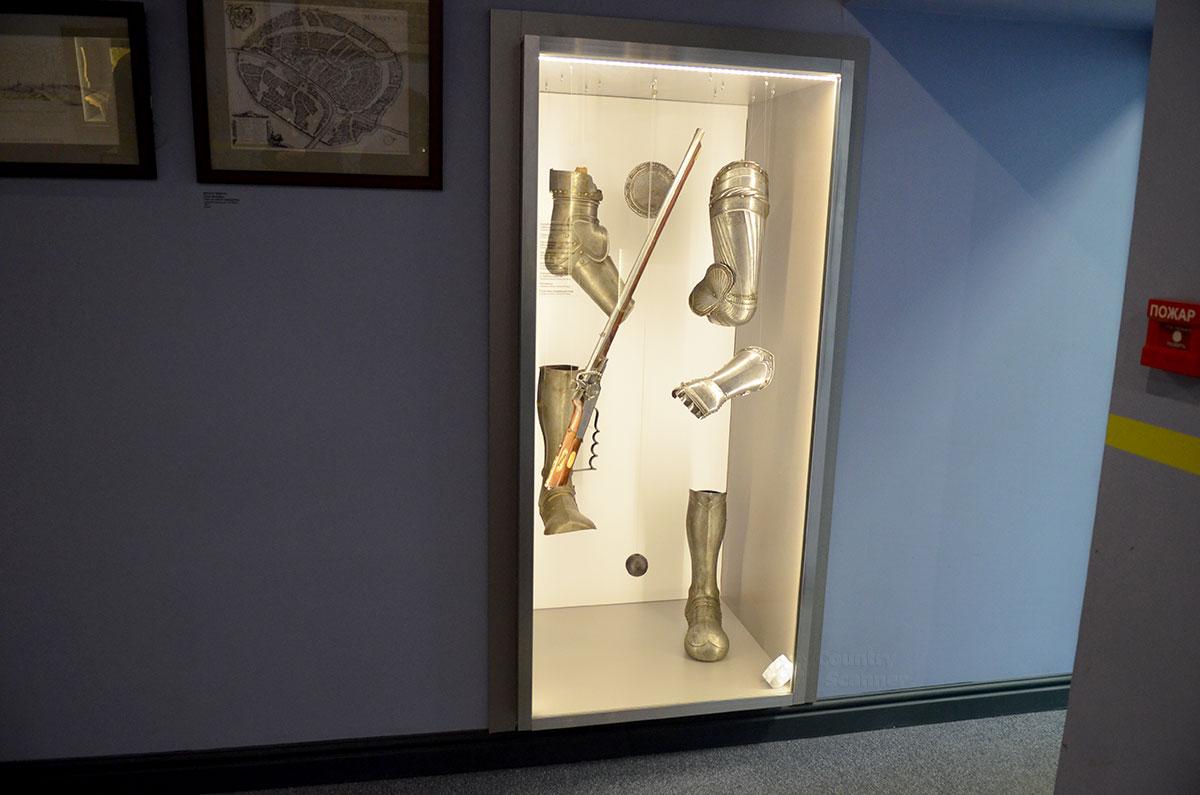 Витрина музея Лефортово, демонстрирующая воинские доспехи. Комплект не собран воедино на манекене, а каждая деталь расположена отдельно, словно предлагается отгадывать ее предназначение.