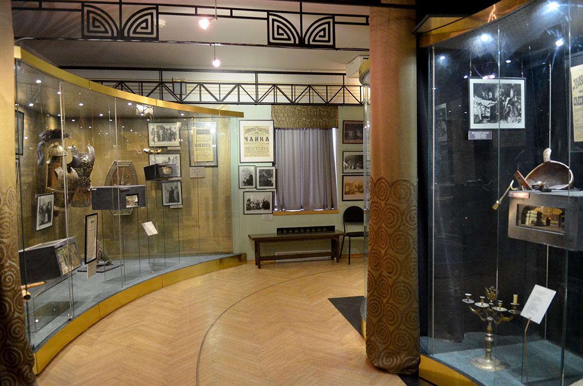 Общий вид одного из залов музея МХАТ с витриной вогнутой формы. Часть чеховского раздела экспозиции, макет занавеса и другие материалы по Чайке на дальней стене.
