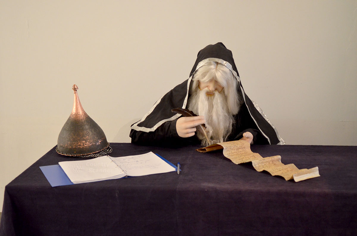 Муляж средневекового летописца в музее Москвы изображает пожилого человека за внесением исторических сведений в архивный свиток. Кованый шлем на краю стола символизирует готовность к сражениям.