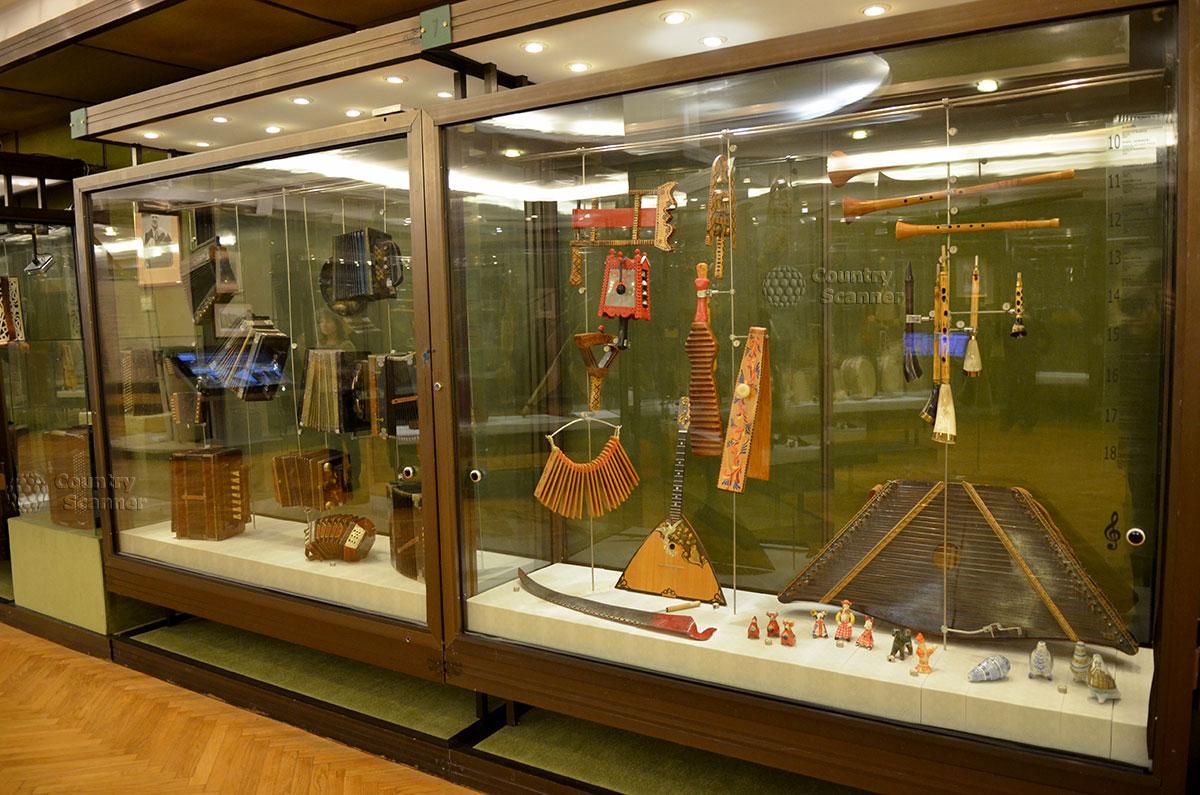 Фрагмент экспозиции русских народных музыкальных инструментов в музее Глинки. Выставлены ударные и струнные инструменты, несколько простейших духовых. Далее – гармоники и баяны.