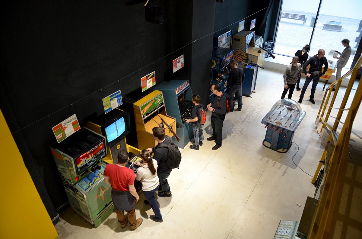 Общий вид скорее игрового, нежели демонстрационного зала музея советских игровых автоматов. Количество посетителей указывает на высокую популярность заведения.
