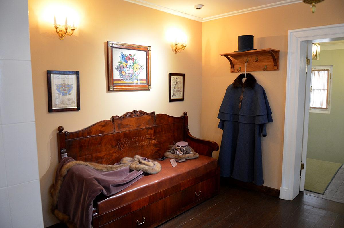 Передняя комната дома музея В.Л. Пушкина меблирована скромно – только диван и вешалка да зеркало напротив. На стене родовой герб, родословное древо и цветочный натюрморт.