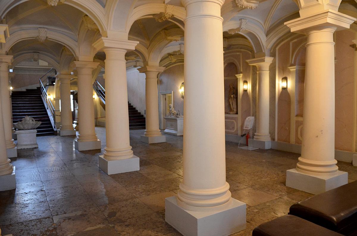 Колоннада в Больших сенях дворца Меншикова на Васильевском острове. В нишах стен античные статуи, предмет на низком постаменте надо рассматривать, подойдя поближе.