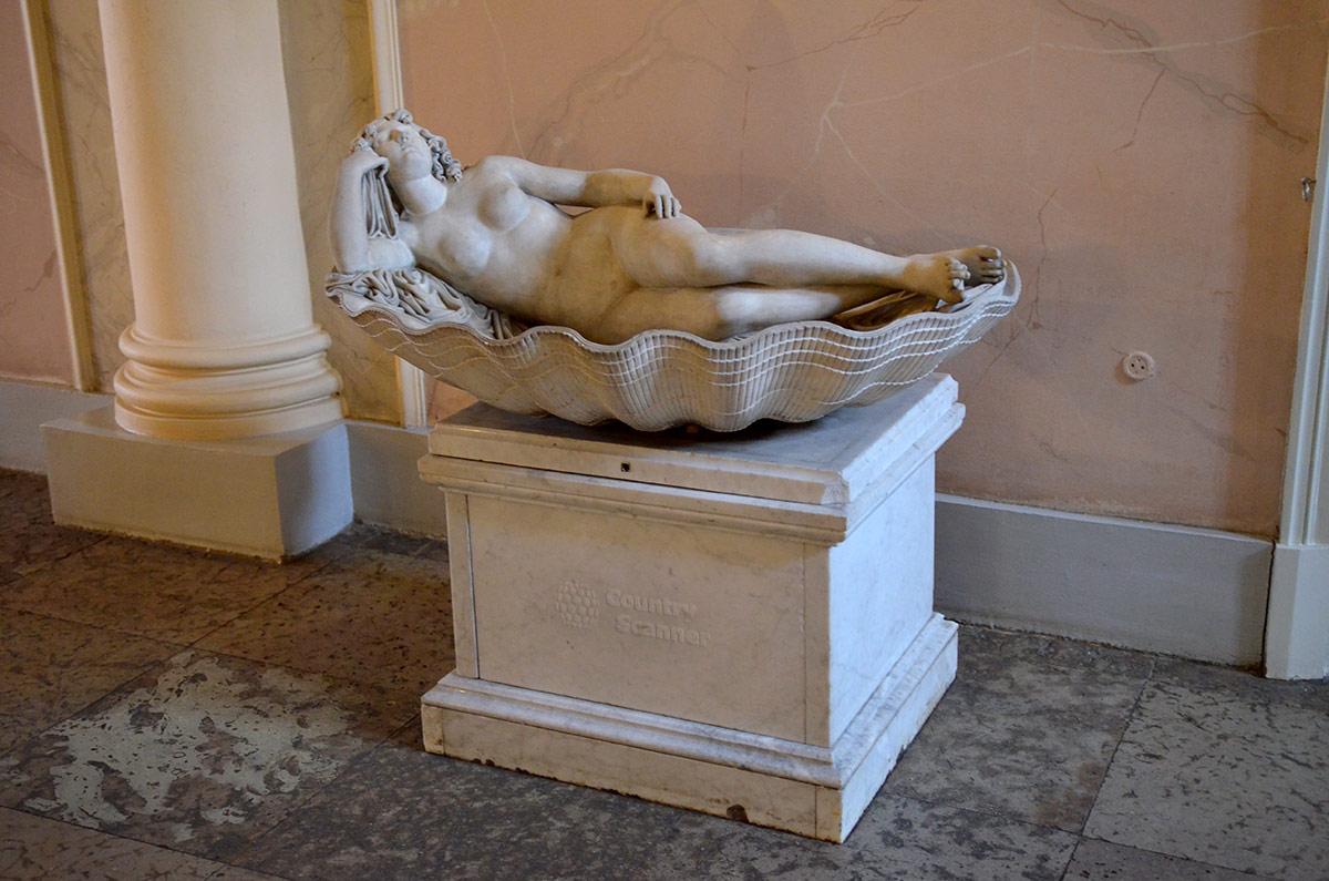 На постаменте скульптура, изображающая возлежащую в раковине гигантского моллюска молодую обнаженную женщину. Это скульптура Венера в раковине француза Кусту.