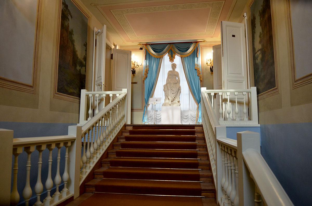 Парадная лестница в доме гвардейского прапорщика Хрущева, где в 1961 году открылся музей Пушкина. На фоне освещенного солнцем окна – женская скульптурная фигура в античных одеяниях.