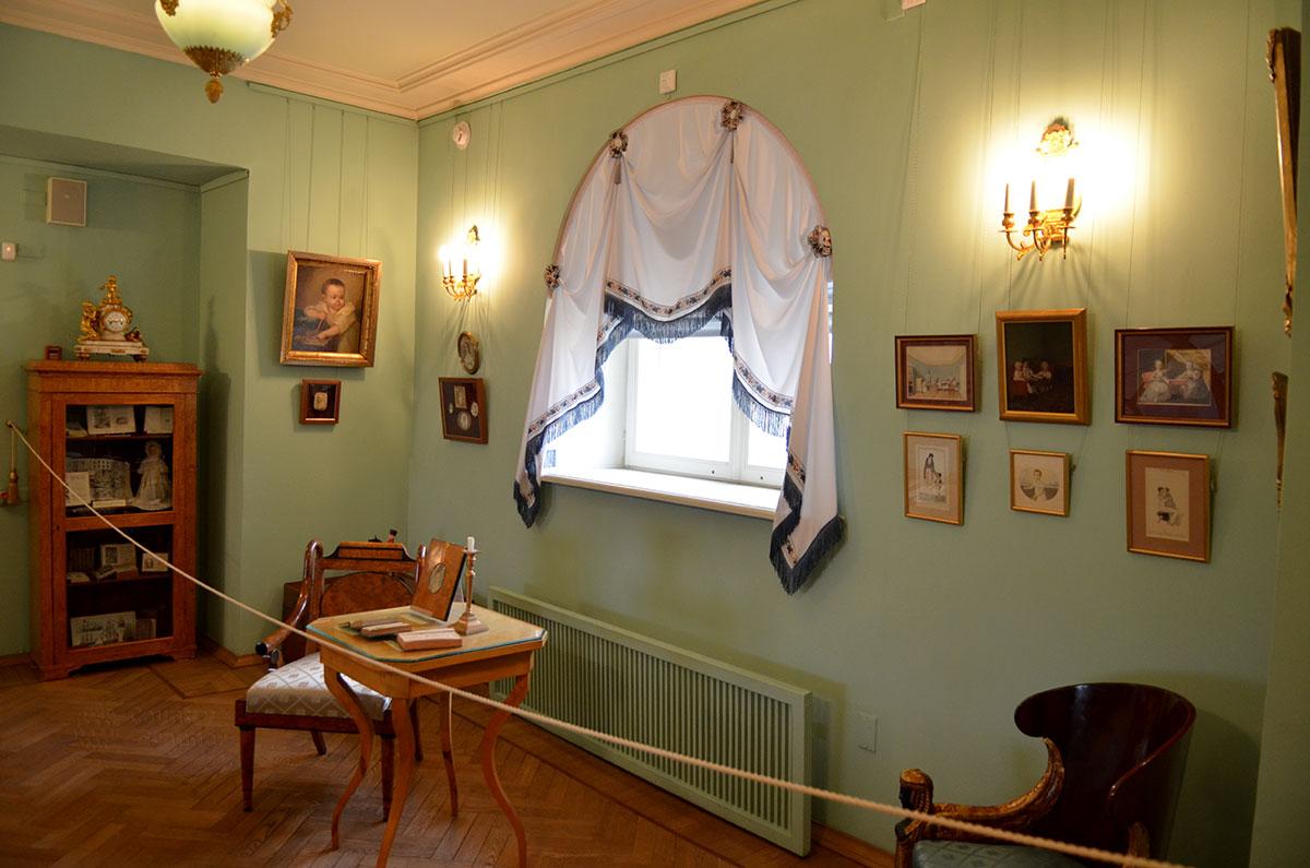 Уголок зала музея Пушкина, рассказывающий о детстве и юности поэта. На квадратном столике свеча и фото, гомеровские поэмы. В самом углу детский портрет Пушкина, выполненный художником де Местром.