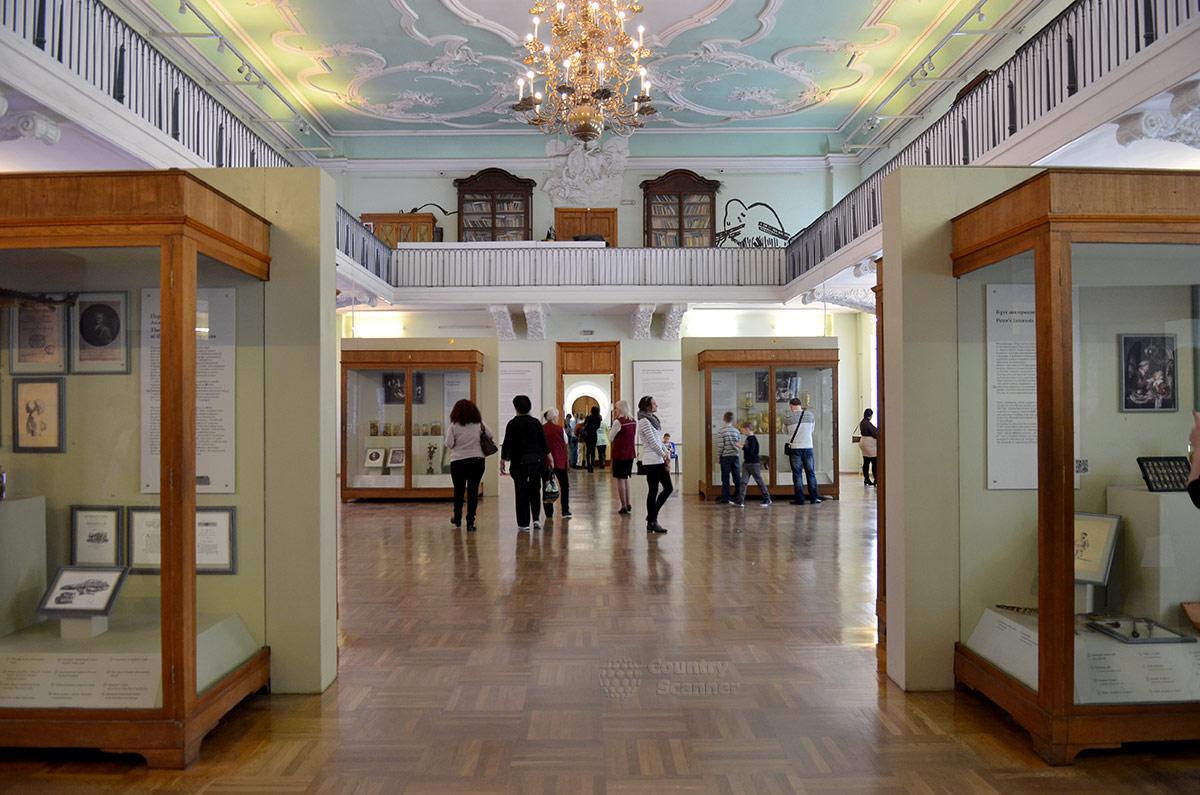 Общий вид находящегося на втором этаже Кунсткамеры зала анатомической экспозиции. Под потолком с красочной лепниной расставлены витрины с редкими экспонатами врожденных аномалий.