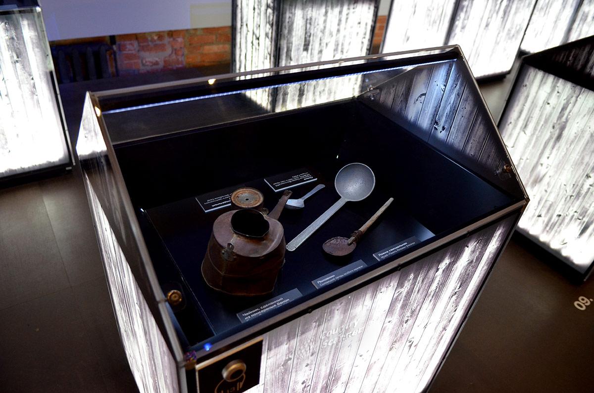 Одна из подсвеченных витрин музея ГУЛАГа с личными вещами заключенных. Здесь и самодельные чайник и ложка, и фабричные изделия.
