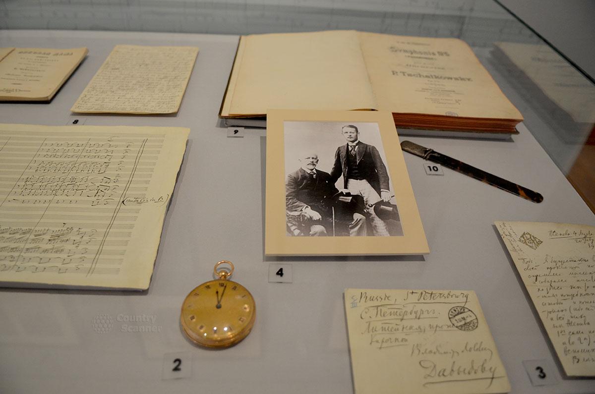 Одна из экспозиций голубого зала музея Чайковского демонстрирует раскрытую книгу, письма и нотные черновики, часы и памятную фотографию Чайковского с товарищем по учебе.