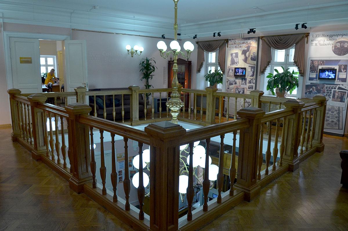 Поднявшись на второй этаж, посетители попадают в просторный холл с межэтажным проемом и помещенной в него массивной люстрой, освещающей одновременно оба этажа.