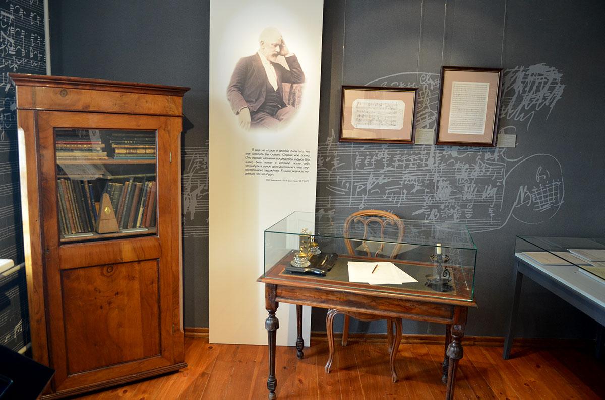 В зале музея Чайковского с темным тоном стен нотные записи на них уже явно чернового характера. Здесь размещены письменный стол и книжный шкаф композитора, его портрет с цитатой.