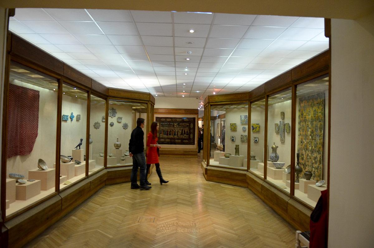 Иранская экспозиция музея Востока, содержащая множество экспонатов, в конце имеет персидский ковер. Сюжет изображения – прием царем Дарием побежденных им владык.