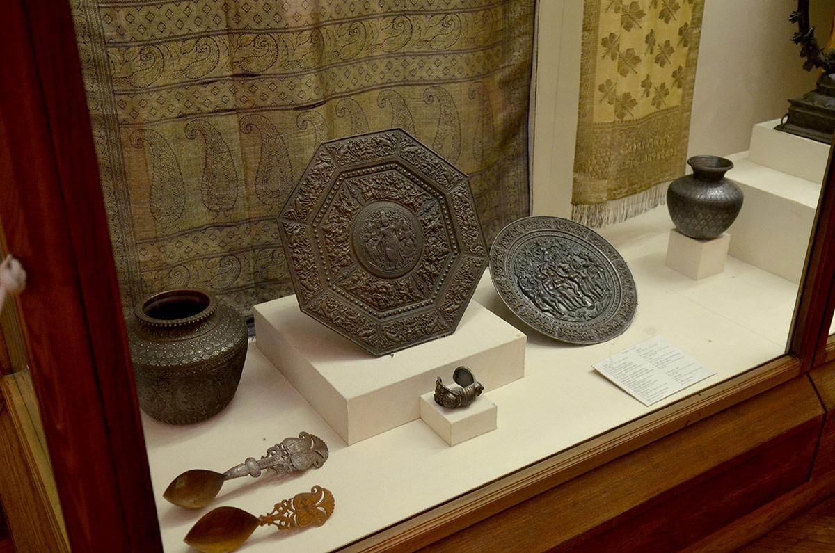Уголок одной из витрин экспозиции индийской культуры и искусства в музее Востока. Изделия из металла представлены сосудами и блюдами разной формы. Барельефы на блюдах искусно выполнены с помощью чеканки.