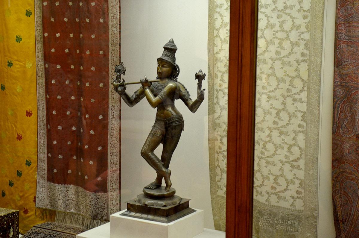 Музей Востока на фоне индийских тканей представляет скульптуру Вишну-Кришны в одном из воплощений. Здесь божество предстает танцующим пастухом, играющим на свирели.