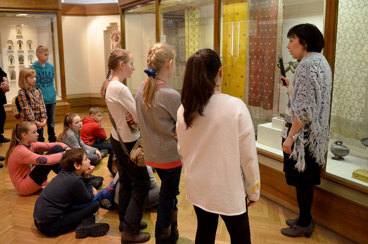 Внимательно слушают юные посетители музея Востока комментарий экскурсовода, рассказывающего о множестве воплощений бога Вишну-Кришны возле статуэтки танцующего пастуха.
