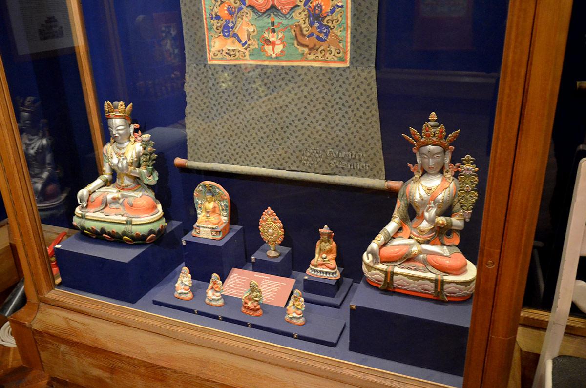 Витрина предметов бурятской культуры и искусства в музее Востока. Ярко раскрашенные статуэтки Будды изготовлены из различных материалов.