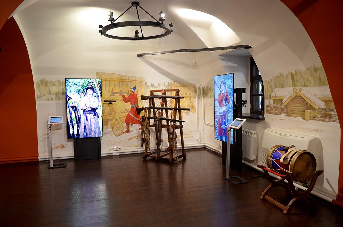 Интерьер интерактивной комнаты для тематических игр посетителей младшего возраста в музее Стрелецкие палаты. Антураж составляют ружейная пирамида и полковой барабан. На стене изображение защитного сооружения Гуляй-город, защитного щита с амбразурами.